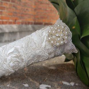 NR.100 ; Pušķa kātiņš iestrādāts romantiskā mežģīnē ar elegantu pērļu rotu.